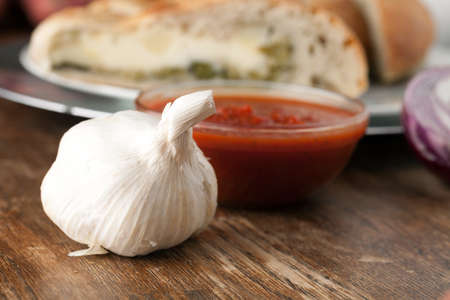 Garlic bulb closeup with tomato sauce and stuffed bread in the background.  Shallow depth of field. Stock Photo