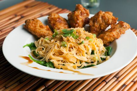 Thaise stijl gebakken kip vleugels op een ronde witte plaat met ei noedels en spinazie.