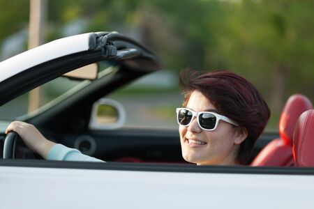 Portret van glimlachende vrouw het besturen van een converteerbare sportwagen met rood lederen interieur. Ondiepe scherptediepte. Stockfoto
