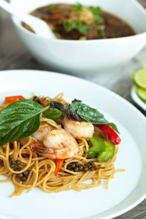 Thai food dishes with shrimp and noodles and soup with duck.  Shallow depth of field.