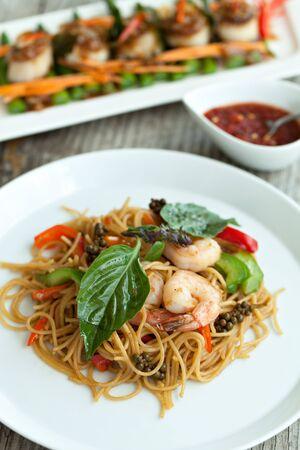 Thais eten gerechten met garnalen en noedels met sint-jakobsschelpen in de achtergrond. Ondiepe scherptediepte.