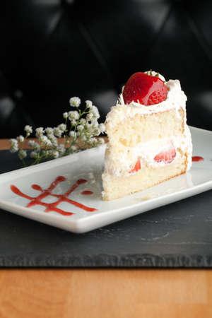 Slice of strawberry shortcake with white chocolate shavings. Standard-Bild