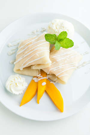 sticky: Thai style tropical dessert crepes filled with fresh mango sticky rice and a scoop of coconut ice cream. Shallow depth of field. Stock Photo