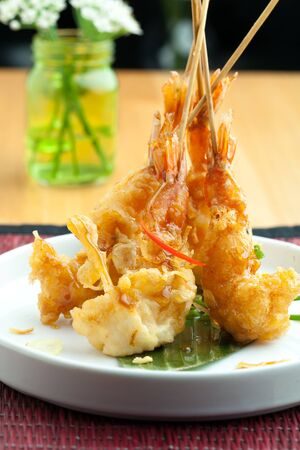 Tempura jumbo shrimp skewers on a white plate standing up vertically. Stock Photo