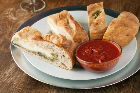 Homemade stromboli or stuffed bread with broccoli potatoes garlic onions and mozzarella cheese along with a side of marinara dipping sauce. Archivio Fotografico
