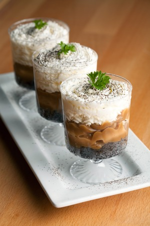 Banana caramel parfait desserts with fresh whipped cream and chocolate cookie crumbles. Shallow depth of field. Stock Photo
