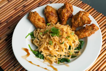 Thai style fried chicken wings on a round white plate with egg noodles and spinach.