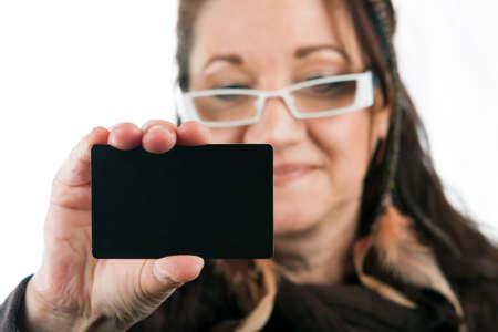Brunette vrouw die een blanco creditcard visitekaartje shoppers club card of gift card van een soort met copyspace. Ondiepe scherptediepte.