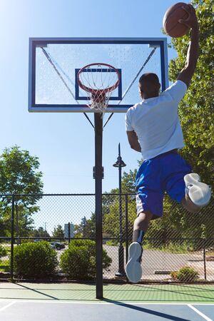Jonge basketbalspeler rijdt naar de hoepel met een hoge vliegende slam dunk. Lichte lens flare.