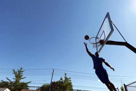 Jonge basketbalspeler rijden naar de hoepel met enkele mooie bewegingen en een kopie ruimte.
