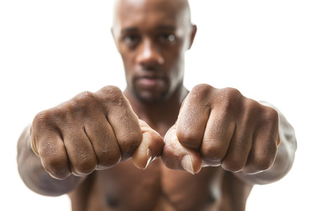 Muscular man of African descent isolated over a white background showing a closeup of his fists and knuckles.  Shallow depth of field.
