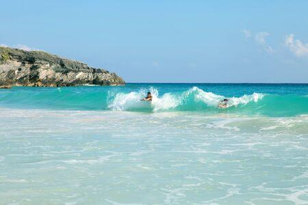 Mensen zwemmen in de golven body surfen op Bermuda's Horseshoe Bay strand. Stockfoto
