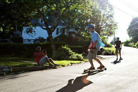 Longboarders schaatsen op een stedelijke weg met lens flare terwijl ze gefilmd door een andere man. Lichte motion blur uit panning techniek om beweging vast te leggen. Stockfoto