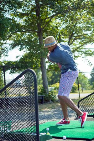 Atletisch golfer swingende op de driving range, gekleed in casual kleding. Stockfoto