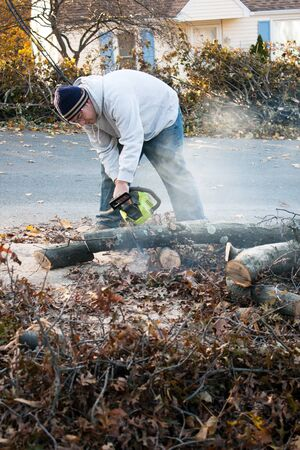 limbs: Man cutting tree limbs with a chainsaw that have fallen from storm damage.  A late fall snow storm in the month of October was the cause.