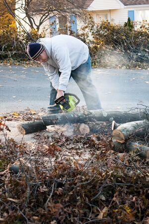 Man snijden van takken met een kettingzaag die zijn gedaald van stormschade. Een late herfst sneeuw storm in de maand oktober was de oorzaak.