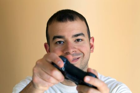 30 something video gamer gaming with his wireless controller. Stock Photo