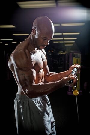bicep: Body builder working out at the gym doing exercises on the cable machine under dramatic lighting.