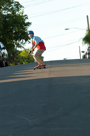 Action shot of a longboarder skating on a suburban road.