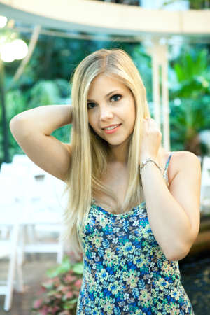 Smiling attractive blonde woman under warm tungsten lighting.