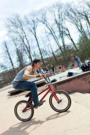 BMX rider athlete riding his bmx bike approaching a jump. Stock Photo
