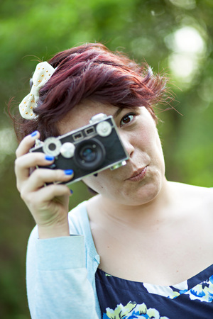 Female Photographer Shooting a vintage slr camera outdoors. Stock Photo