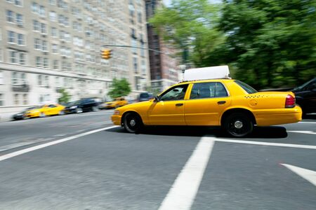 Yellow NYC taxi cab speeding by during daytime.  Slow shutter speed panning technique used for motion blur.