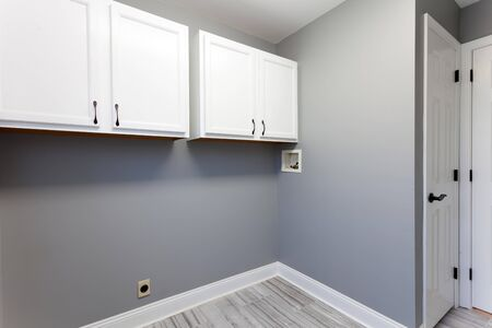 Empty laundry room setup with electrical plumbling hookups and cabinets in a modern home. Stock Photo