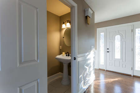 entryway: Beautiful staged entryway interior and half bathroom in a modern house. Stock Photo