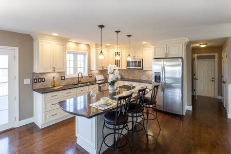 Mooie opgevoerd keuken kamer in een modern huis met granieten aanrecht en antieke afgewerkte kasten. Stockfoto