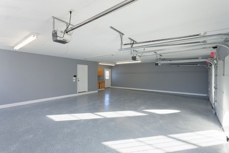 Beautiful brand new three car garage interior with finished floors and work space. Stock Photo