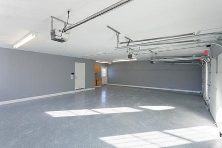 Mooie nieuwe drie auto garage interieur met afgewerkte vloeren en werkruimte.