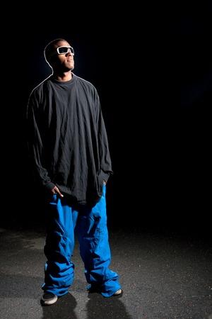 Afro-Amerikaanse jonge man met wijde winter sportkleding poseren onder dramatische verlichting met lens flare.