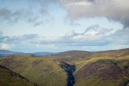View looking east above Glen Doll towards rolling Scottish mountains with white clouds 免版税图像