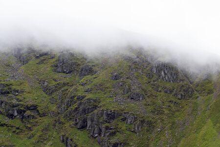 White cloud rolling down over rocky Scottish hillside