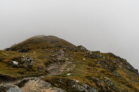 View towards empty cloud beyond over the edge of a green rocky Scottish hilltop