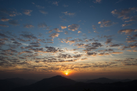 scatters: sunrise with scattered clouds sky and the dark mountain foreground