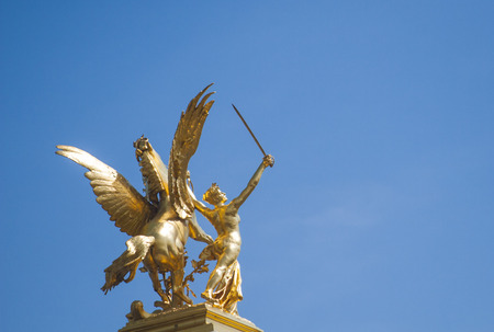 Golden statue of a winged horse and naked woman holding a sword from behind with blue sky Alexander III Bridge