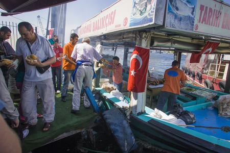 Fish kebab vendor on boat doing transaction Istanbul