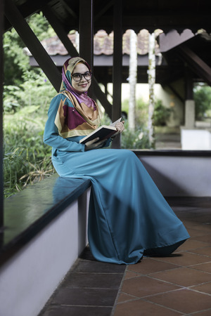 Woman wearing hijab sitting and holding opened book