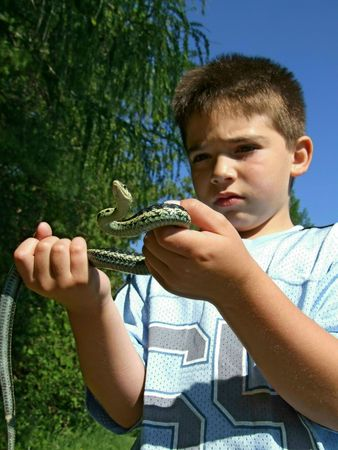 fear child: Kenny nervously holds a large garter snake. He appears to be wondering, What do I do now?