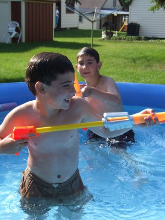 seven year old: Day one with my new camera and, to make it more interesting, I purchased several pool toys for the boys to use as props. The boys were having so much fun, the neighbours were looking out to see what all the commotion was about. Here Kenny aims his water g Stock Photo