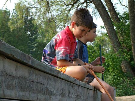 chłopięctwo: Dwóch chłopców siedzi na portach ryb z sieci. Zdjęcie Seryjne