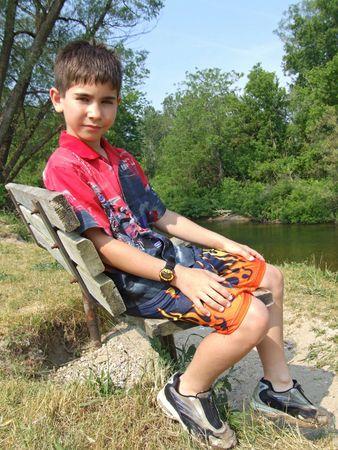 chłopięctwo: A chłopak siedzi na ławce z widokiem na rzekę.