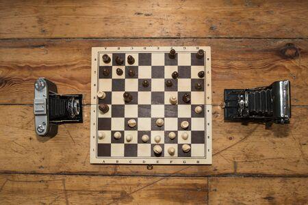 jugando ajedrez: dos cámaras del vintage que juegan a ajedrez en un tablero de madera colocado en alguna Flu madera