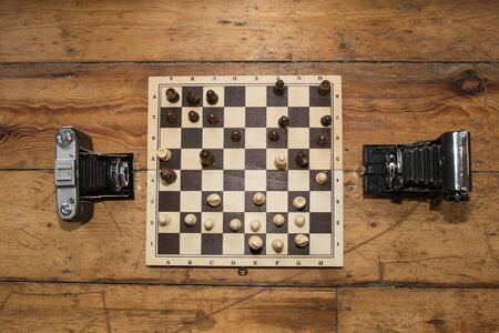 floo: two vintage cameras  playing chess on a wooden board set on some wooden floo Stock Photo