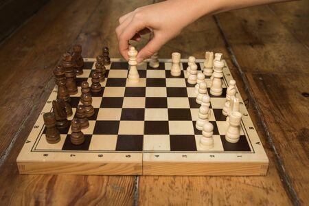 jugando ajedrez: una sola mano jugando al ajedrez en un tablero de madera situado en algún piso de madera