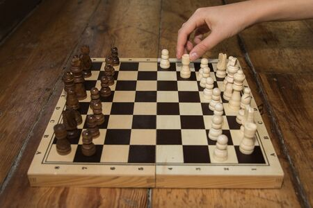 jugando ajedrez: a single hand playing chess on a wooden board set on some wooden floor Foto de archivo