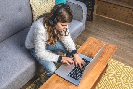 conservatory: Teenage girl in the Conservatory with nordic sofa, laptop and headphone, wooden floor, yellow rug