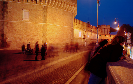 admirers: Castel SantAngelo in Rome at night. The crowd is in fast motion, admiring it.